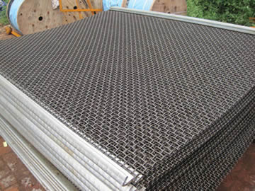 A stack of crimped trommel screen mesh with hooked edge.