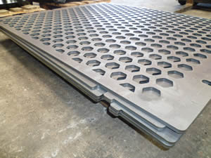 A stack of hexagonal perforated vibrating screen mesh is on the ground.