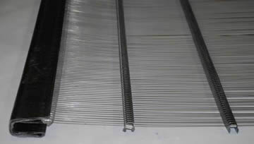 A piece of piano wire screen with two metal sliding bars.